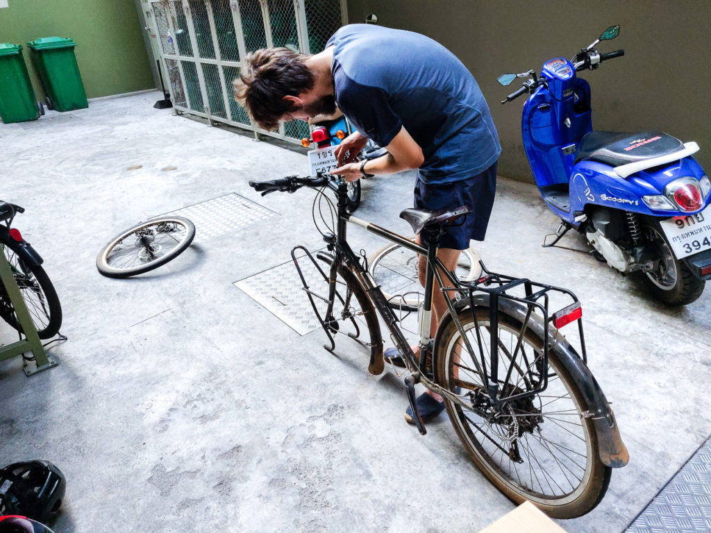 Armand disassembling his bicycle in Bangkok
