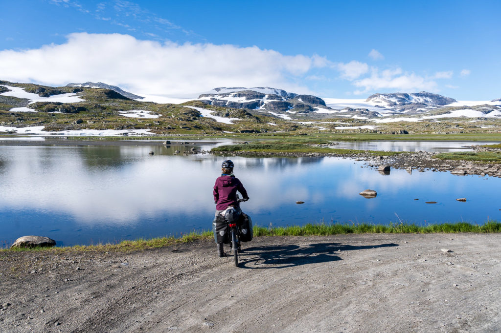 Johanna on the Rallarvegen in front of the Ustekveikja & Hardangerjøkulen in the background