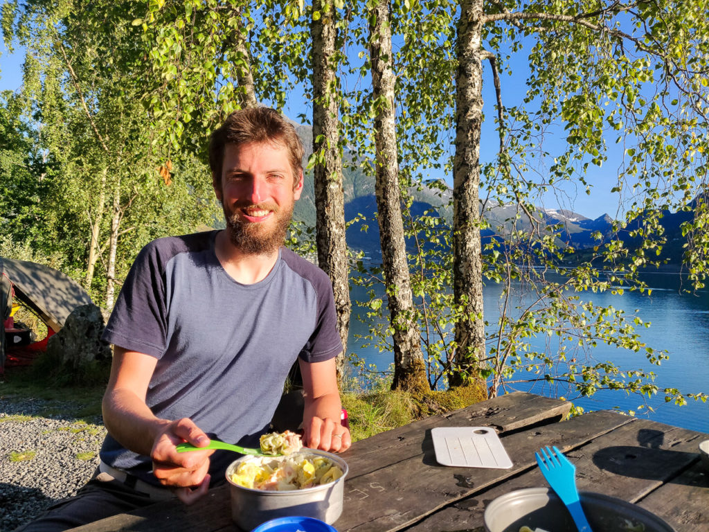 Armand eating tortellini with salmon and leek at our wild camping spot along the Innvikfjorden
